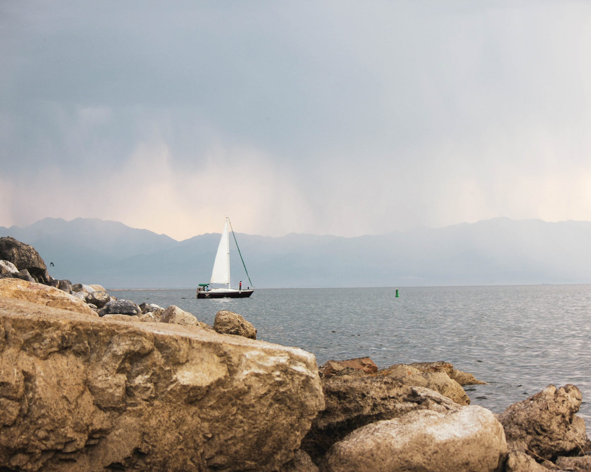 A view of a sailboat in the great salt lake from the rocky beach